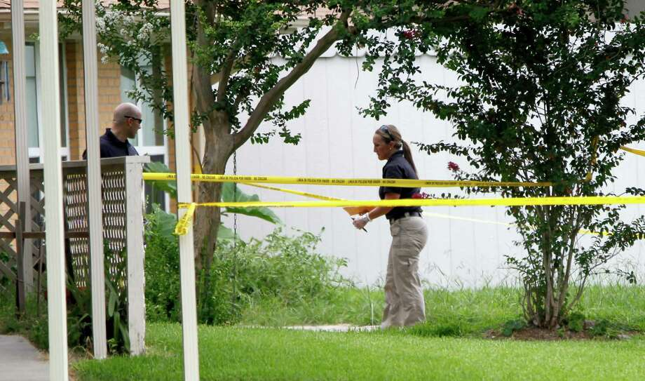 Pasadena police officers investigate the shooting death of a woman at her front doorstep in the 3100 block of Redfield Drive on Saturday. Photo: Karen Warren, Staff / © 2014 Houston Chronicle