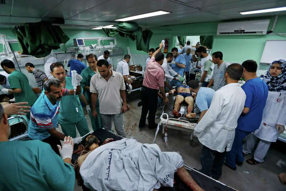Medics work on Palestinians wounded during Israeli strikes, at the emergency room of the Kamal Adwan hospital in Beit Lahiya on Saturday. According to the hospital, more than 35 wounded Palestinians arrived at the hospital Saturday, five with serious wounds, and three were dead on arrival. Photo: Lefteris Pitarakis, STF / AP
