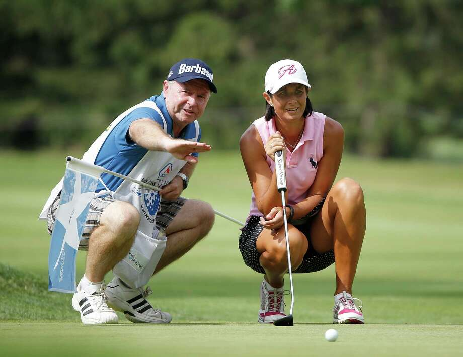 Tournament co-leader Laura Diaz gets a helping hand from caddie Pete Smith on the 17th green during third-round play of the Marathon Classic. Photo: Gregory Shamus, Stringer / 2014 Getty Images