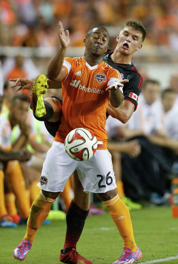 Houston Dynamo midfielder Corey Ashe (26) and Toronto FC defender Nick Hagglund (17) battle to keep the ball in play during the first half of the MLS soccer game at BBVA Compass Stadium, Saturday, July 19, 2014, in Houston. Photo: Karen Warren, Houston Chronicle / © 2014 Houston Chronicle