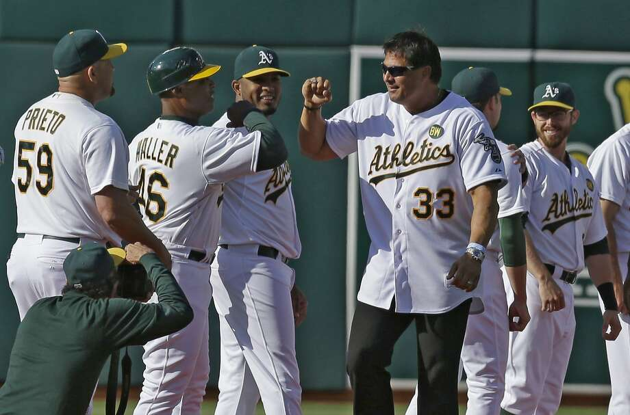 Jose Canseco (33) greets first base coach Tye Waller (46) and current A's players during a pregame ceremony honoring the 1989 world champs. Photo: Ben Margot, Associated Press