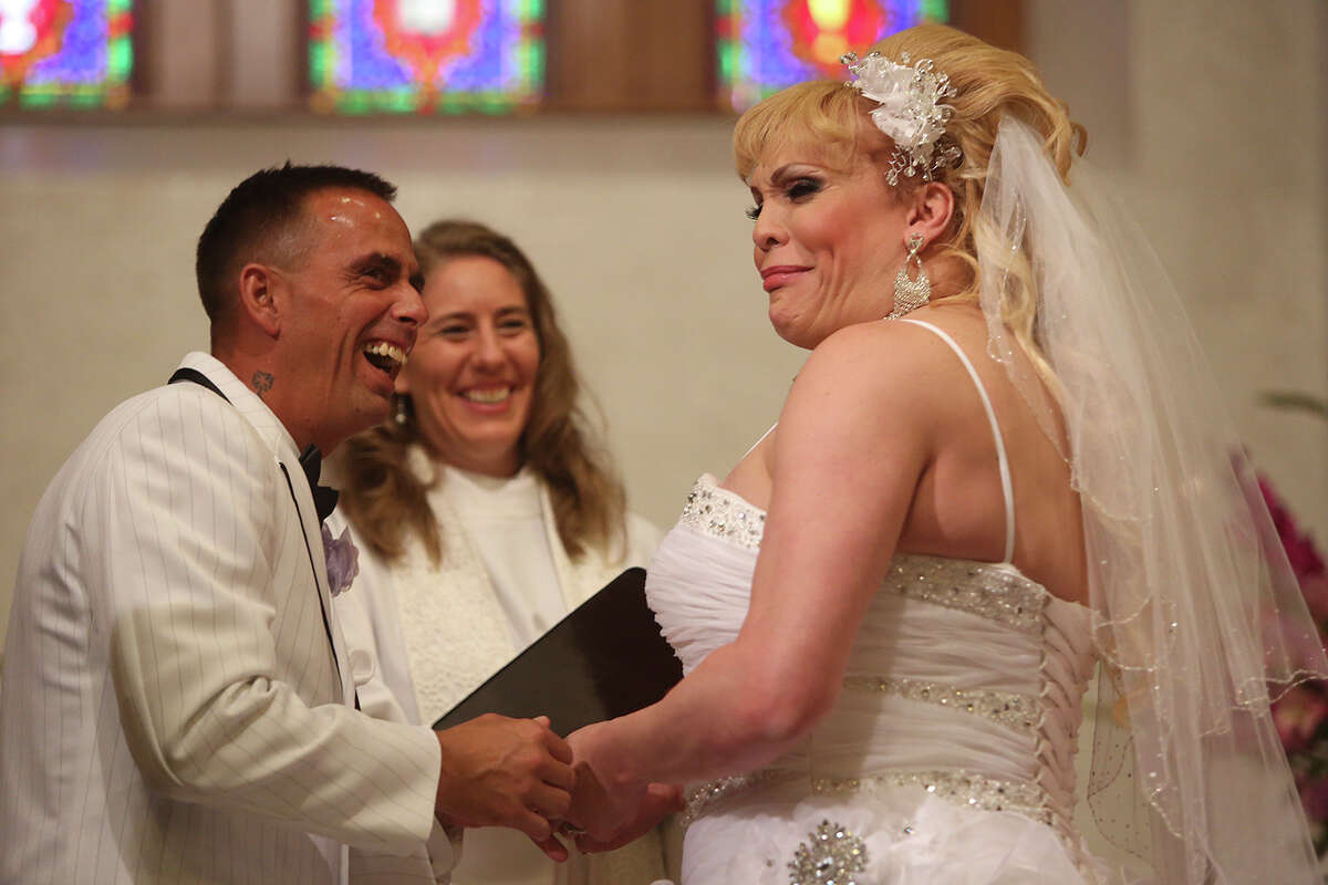 Alexis Valerio and Frank Davis laugh with Rev. Lura Groen as they exchange rings during their wedding at Grace Lutheran Church in Houston on Saturday, July 19, 2014.