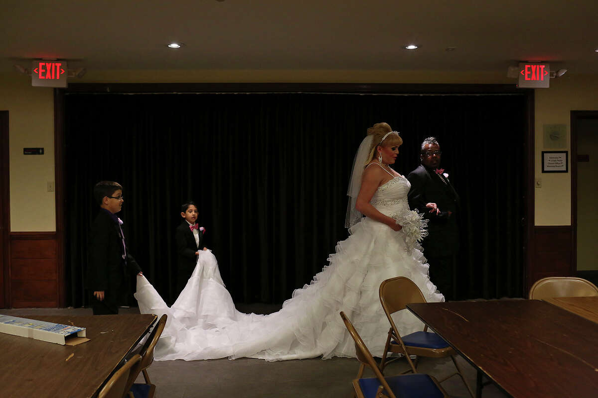 Alexis Valerio walks with Chris Wilson, a man who was like a father to her since she was in high school and came out as gay in San Antonio, while Frank O'Connor, 10, left, and Samuel Guzman, 6, carry her 12-foot-train, as she walks to enter the church to marry Frank Davis at Grace Lutheran Church in Houston on Saturday, July 19, 2014.