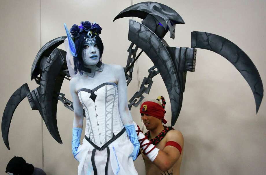 Christian Degalicia of Las Vegas, dressed as Lee Sin from League of Legends, adjusts the dress of his wife, Vanessa Degalicia, dressed as Ghost Bride Morgana at San Japan: Samurai 7 on Saturday. Photo: Photos By Timothy Tai / San Antonio Express-News / © 2014 San Antonio Express-News