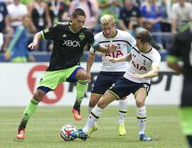 Seattle Sounders' Clint Dempsey, left, battles Tottenham Hotspur's Lewis Holtby, center, and Ryan Mason for the ball during the second half of a friendly soccer match in Seattle, Saturday, July 19, 2014. The match ended in a 3-3 draw. (AP Photo/Stephen Brashear)