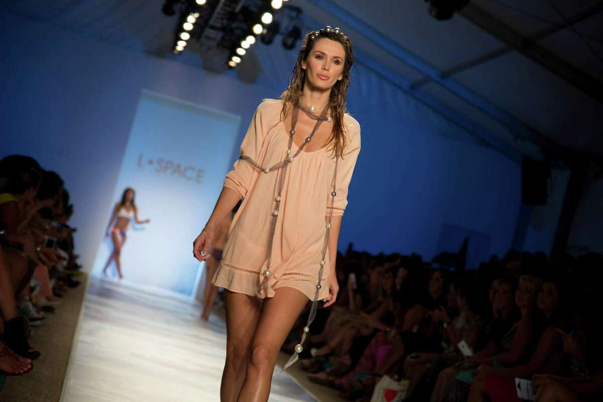 A model walks down the runway wearing swimwear from the L*Space by Monica Wise collection during the Mercedes-Benz Fashion Week Swim show, Saturday, July 19, 2014, in Miami Beach, Fla.