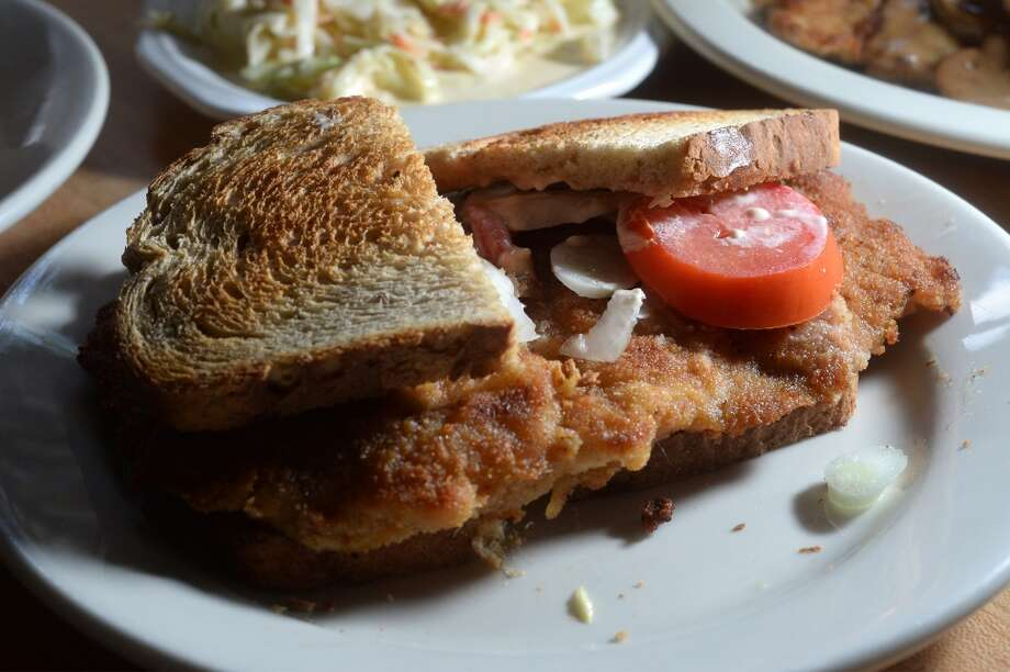 Schnitzel sandwich with tomatoes and onion at Schnitzel in Vidor. The German style restaurant offers schnitzel, kraut and sausage. Photo taken Monday, July 07, 2014 Guiseppe Barranco/@spotnewsshooter