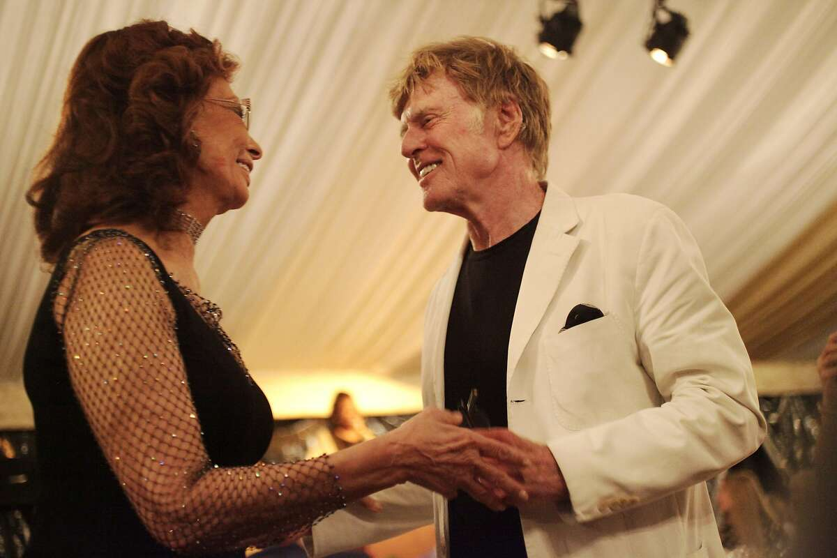 Sophia Loren and Robert Redford share a moment together after the tribute dinner for Loren during the annual Festival del Sole, featuring