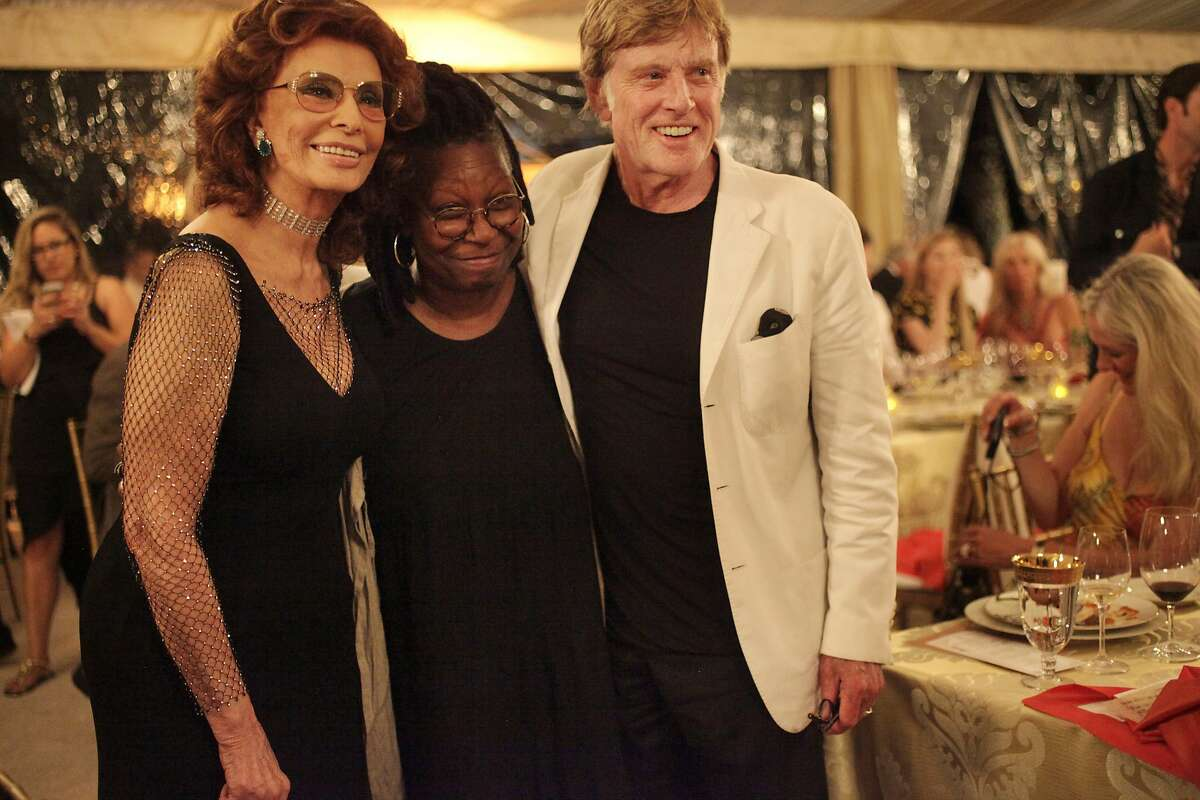 """From left, Sophia Loren, Whoopi Goldberg and Robert Redford pose for a photo together after dinner during the annual Festival del Sole, featuring """"Bella Italia: A Tribute to Sophia Loren"""" July 19, 2014 at the Far Niente Winery in Oakville, Calif. Maestro Carlo Ponti debuted LA Virtuosi Orchestra with a tribute concert to his mother, Sophia Loren. The American composer Daniel Brewbaker was commissioned to write the piece, called """"Sinfonietta per Sofia"""". Following the concert was a tribute dinner to Loren, hosted by Whoopi Goldberg, including presenters Francis Ford Coppolla and Robert Redford."""
