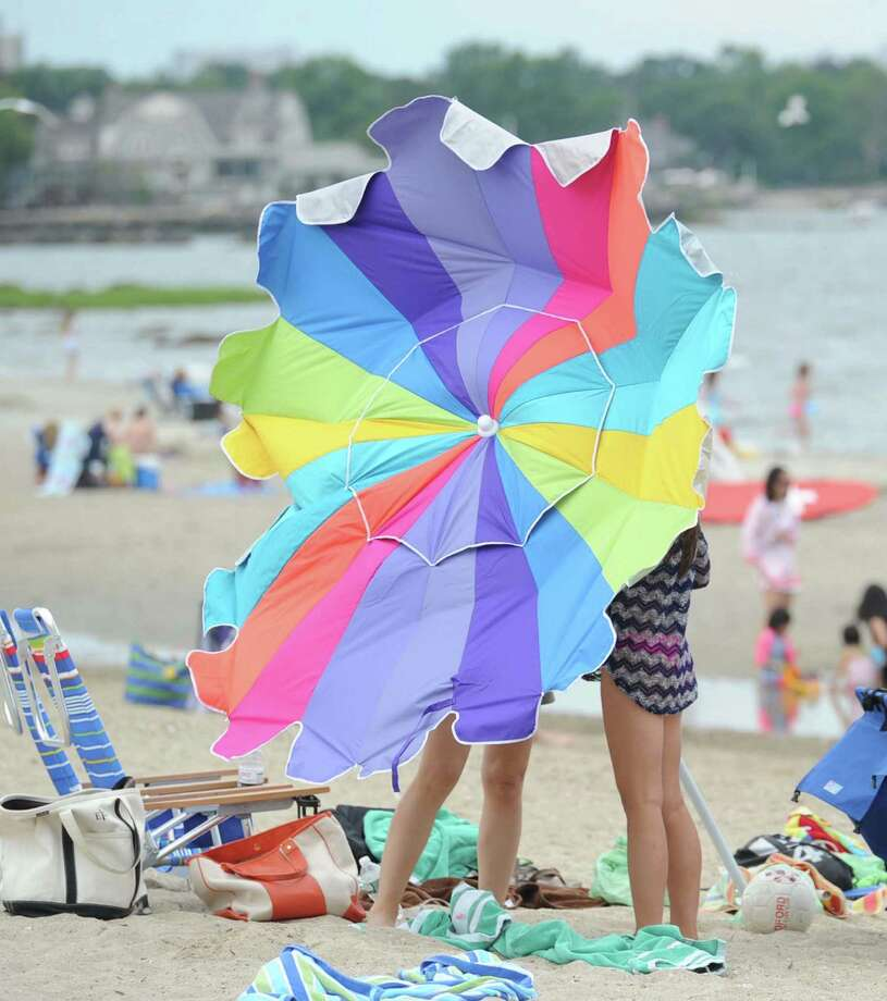 No, that is not the NBC peacock strutting on the sands of Greenwich Point. It is two sunbathers battling a beach umbrella as a breeze kicks up. Photo: Bob Luckey / Greenwich Time