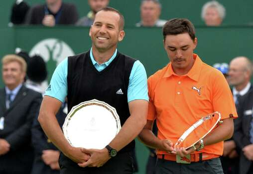 Spain's Sergio Garcia (L) and US golfer Rickie Fowler stand with their second place trophies after finishing two strokes behind winner, Northern Ireland's Rory McIlroy at Royal Liverpool Golf Course in Hoylake, north west England on July 20, 2014. McIlroy won the British Open at Royal Liverpool Golf Course in Hoylake with a final round of 71. The 25-year-old Northern Irishman won with a seventeen under par total of 271, two strokes clear of Rickie Fowler and Sergio Garcia. AFP PHOTO / PAUL ELLISPAUL ELLIS/AFP/Getty Images Photo: PAUL ELLIS, AFP/Getty Images / AFP