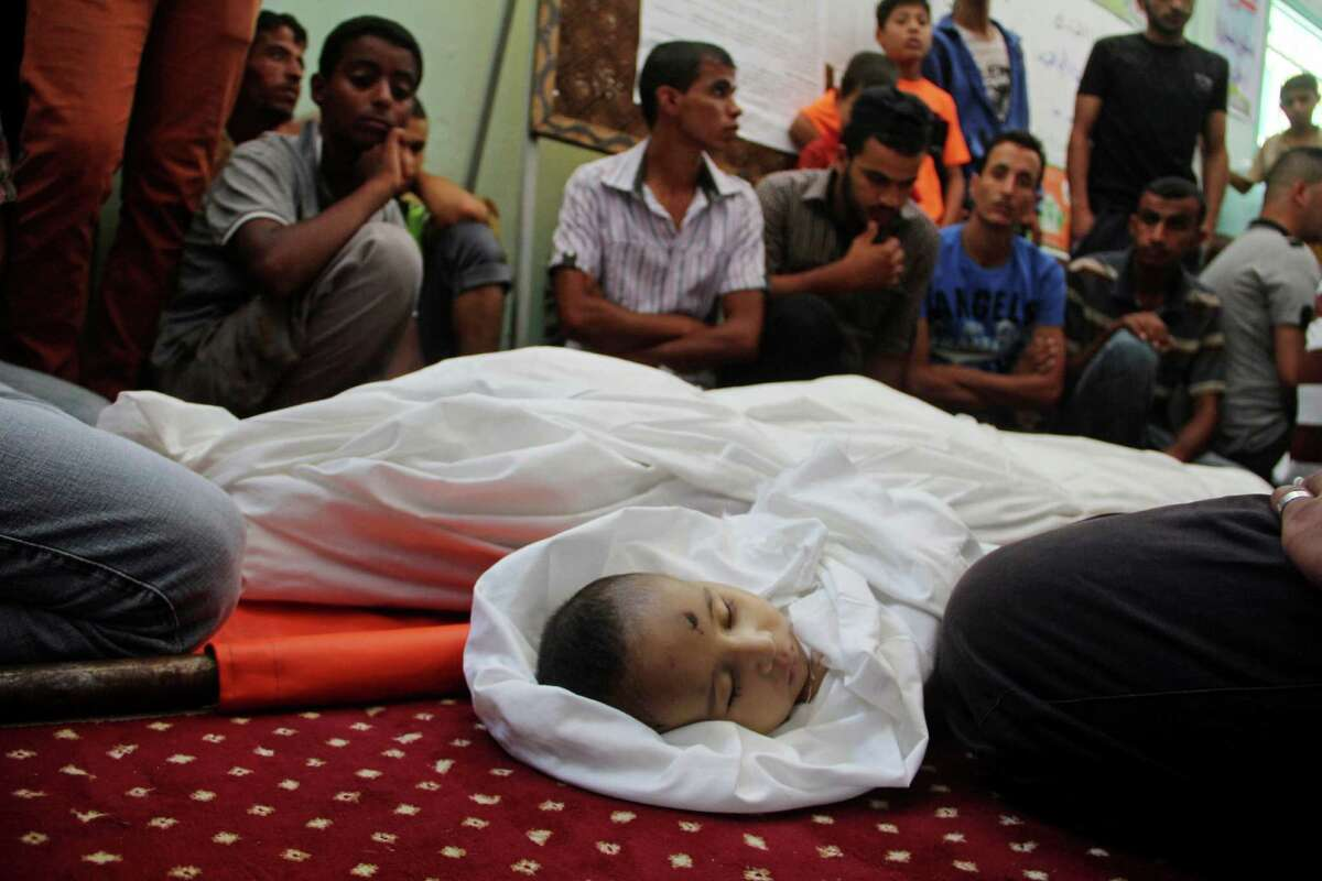 Palestinian relatives mourn over the bodies of Omar al-mahmom, 18, left, and 3-month-old Fares el-Trabeen al-mahmom during their funeral in Rafah, southern Gaza Strip, Friday, July 18, 2014. The two were killed in an Israeli air strike at their family home. Israeli troops pushed deeper into Gaza on Friday to destroy rocket launching sites and tunnels, firing volleys of tank shells and clashing with Palestinian fighters in a high-stakes ground offensive meant to weaken the enclave's Hamas rulers. Latest from AP: Scores dead in first major ground battle in Gaza