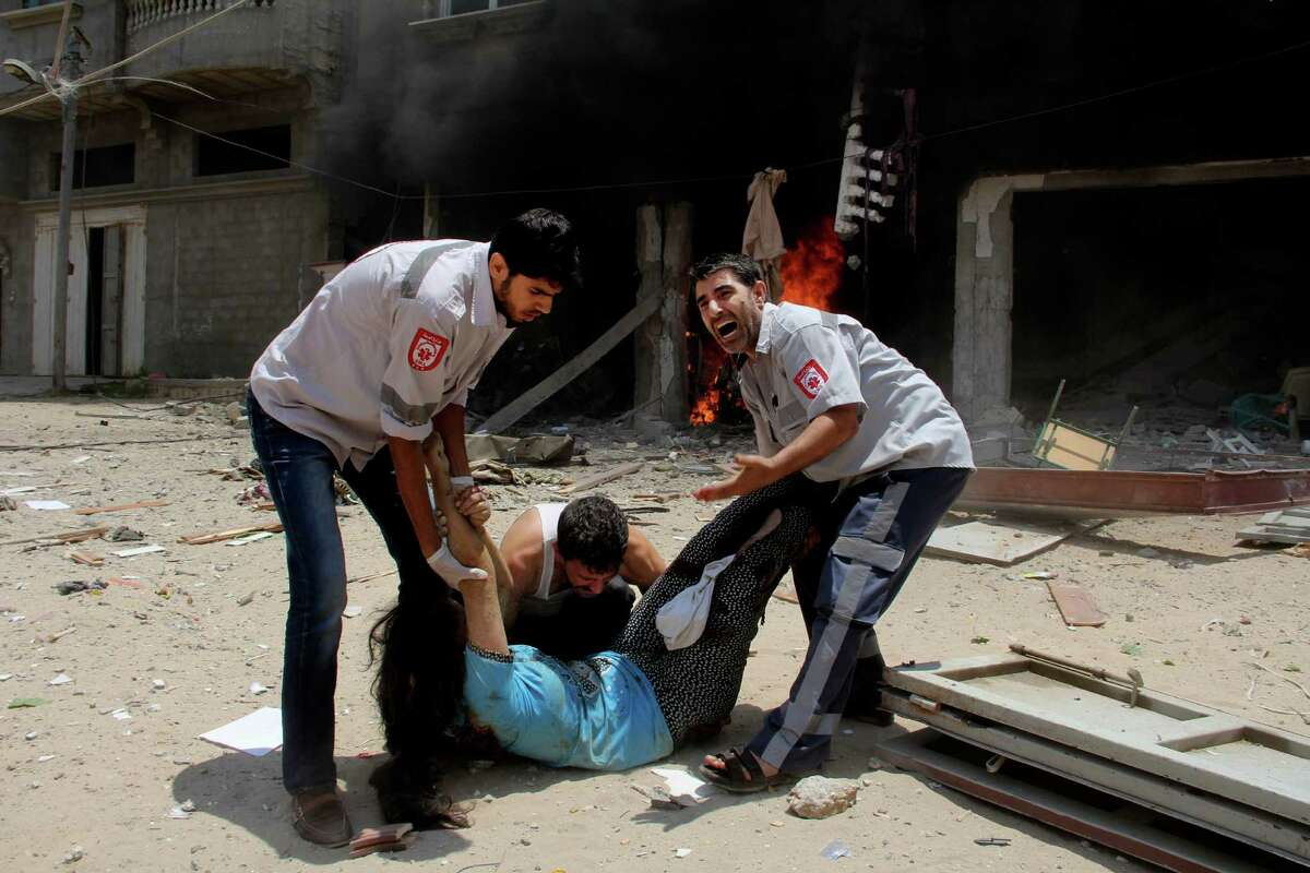 Palestinian medics help carry a wounded woman in front of the Al Mughrabi family building following an Israeli air strike that hit their home in Rafah, Sunday, July 20, 2014. One woman and her 2-year-old grandson were killed when an Israeli airstrike struck the home of the Mughrabi family northeast of Rafah, according to the Red Crescent.Latest from AP: Scores dead in first major ground battle in Gaza