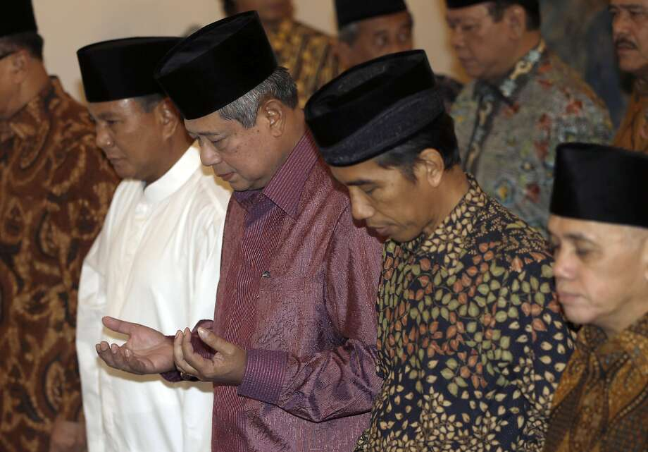 Indonesian President Susilo Bambang Yudhoyono (center) prays with candidates Prabowo Subianto (left) and Joko Widodo at the State Palace. Photo: Dita Alangkara, Associated Press
