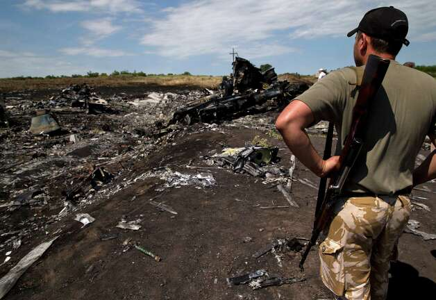 An armed man looks at charred debris at th