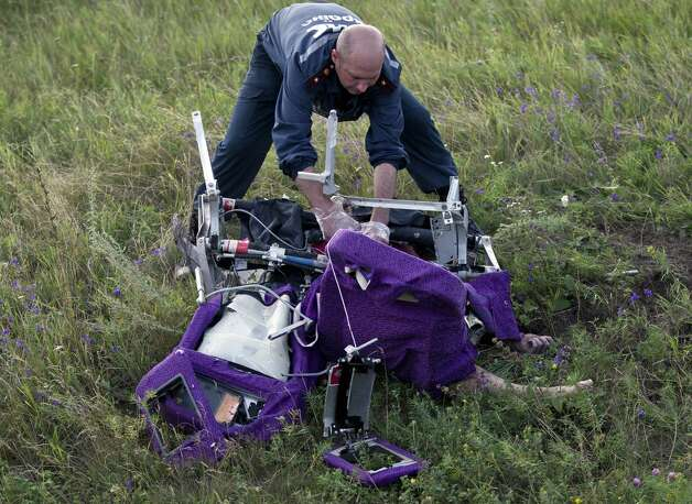 An emergency worker cuts through aircraft seat belts to free the body of a victim at the crash site of Malaysia Airlines Flight 17 near the village of Hrabove, eastern Ukraine, Saturday, July 19, 2014. International monitors moved gingerly Saturday through fields reeking of the decomposing corpses that fell from a Malaysian airliner shot down over rebel-held eastern Ukraine, trying to secure the sprawling site in hopes that a credible investigation can be conducted. Photo: Vadim Ghirda, AP / AP