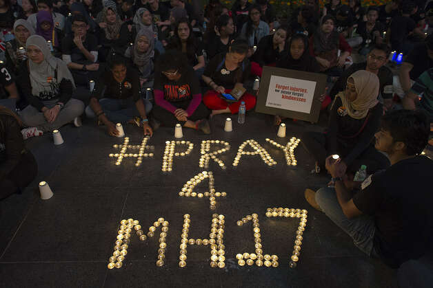 People gather during a candle-light vigil for the victims of the Malaysia Airlines flight MH17 from Amsterdam to Kuala Lumpur, at a shopping mall in Kuala Lumpur on July 18, 2014. A Malaysia Airlines Flight MH17 carrying 298 people from Amsterdam to Kuala Lumpur crashed on July 17 in rebel-held east Ukraine, as Kiev said the jet was shot down in a 'terrorist' attack. Photo: NICOLAS ASFOURI, Wire Photos / AFP