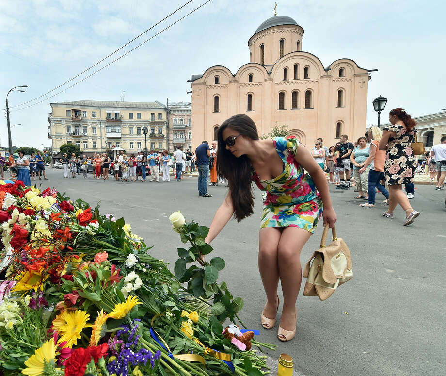 A girl lay flowers as people lay flowers and light candles in front of the Embassy of the Netherlands in Kiev on July 18, 2014, to commemorate passengers of Malaysia Airlines flight MH17 carrying 295 people from Amsterdam to Kuala Lumpur which crashed in eastern Ukraine.  Ukraine's prime minister said Friday that pro-Russian separatist rebels that Kiev believes shot down a Malaysian airliner with 298 people on board should face an international tribunal The Hague. Photo: SERGEI SUPINSKY, Wire Photos / AFP