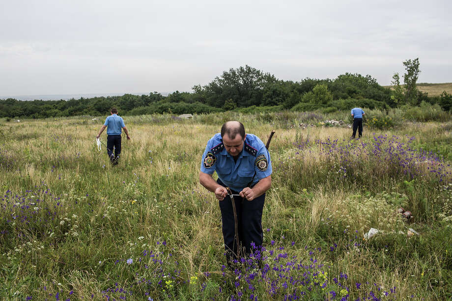 A Ukrainian police officer ties a white ribbon to a stake to mark human remains found in a field on July 18, 2014 in Grabovka, Ukraine. Air Malaysia flight MH17 traveling from Amsterdam to Kuala Lumpur crashed yesterday on the Ukraine/Russia border near the town of Shaktersk. The Boeing 777 was carrying 298 people including crew members, the majority of the passengers being Dutch nationals, believed to be at least 173, 44 Malaysians, 27 Australians, 12 Indonesians and 9 Britons. It has been speculated that the passenger aircraft was shot down by a surface to air missile by warring factions in the region. Photo: Brendan Hoffman, Getty Images / 2014 Getty Images