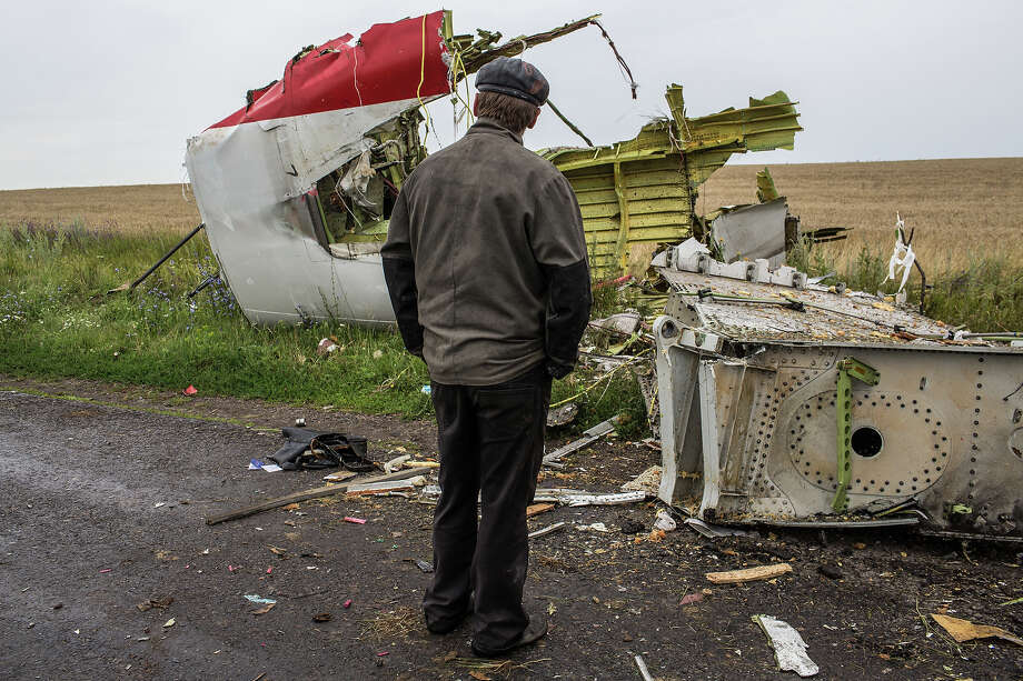 A man looks at the wreckage of passenger plane Air Malaysia flight MH17 on July 18, 2014 in Grabovka, Ukraine. Air Malaysia flight MH17 traveling from Amsterdam to Kuala Lumpur crashed yesterday on the Ukraine/Russia border near the town of Shaktersk. The Boeing 777 was carrying 298 people including crew members, the majority of the passengers being Dutch nationals, believed to be at least 173, 44 Malaysians, 27 Australians, 12 Indonesians and 9 Britons. It has been speculated that the passenger aircraft was shot down by a surface to air missile by warring factions in the region. Photo: Brendan Hoffman, Getty Images / 2014 Getty Images