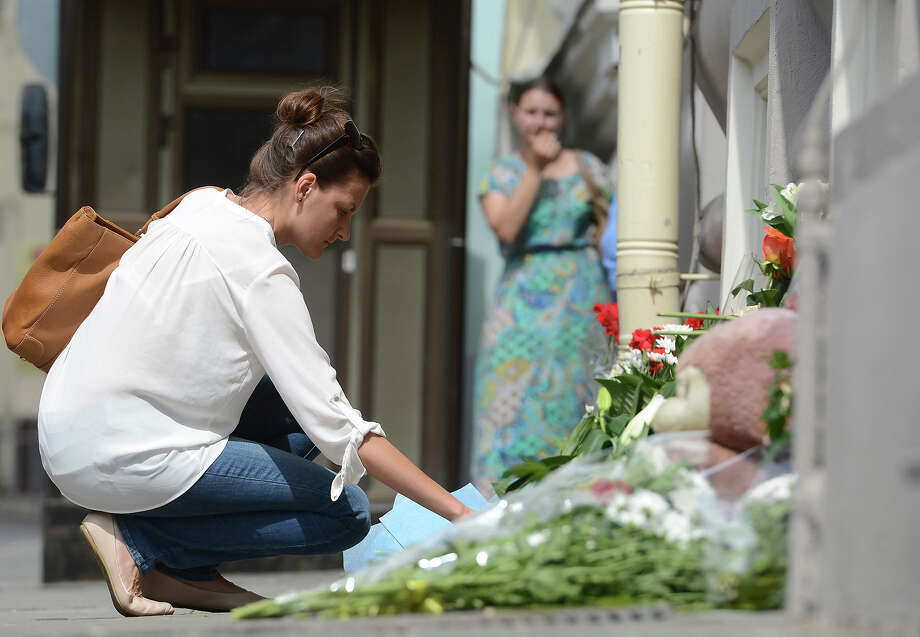Russian and Dutch citizens light candles and lay flowers in front of the Embassy of the Netherlands for passengers, died in the crash of Malaysia Airlines Boeing 777 carrying 295 people from Amsterdam to Kuala Lumpur at close to Russia's border with Ukraine, in Moscow, Russia on July 18, 2014. Photo: Anadolu Agency, Getty Images / 2014 Anadolu Agency
