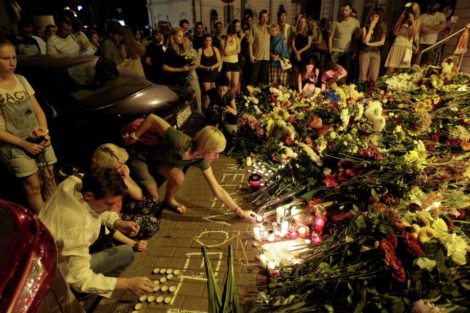People hold candles and place flowers outside the Dutch embassy in in Kiev, Ukraine, to honor the victims of the Malaysia Airlines plane crash on Thursday, July 17, 2014.  Photo: Sergei Chuzavkov, AP / AP