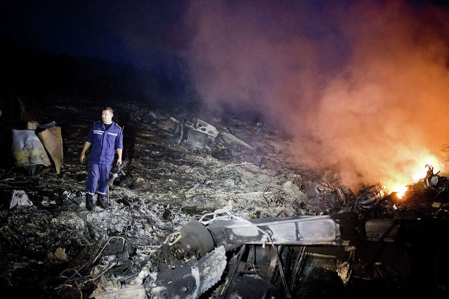 Debris from Malaysia Airlines Flight 17 is shown smouldering in a field  July 17, 2014 in Grabovo, Ukraine near the Russian border. Flight 17, on its way from Amsterdam to Kuala Lumpur and carrying 295 passengers and crew, is believed to have been shot down by a surface-to-air missile, according to U.S. intelligence officials Ukrainian authorities quoted in published reports. The area is under control of pro-Russian militias. Photo: Pierre Crom, Getty Images / 2014 Pierre Crom