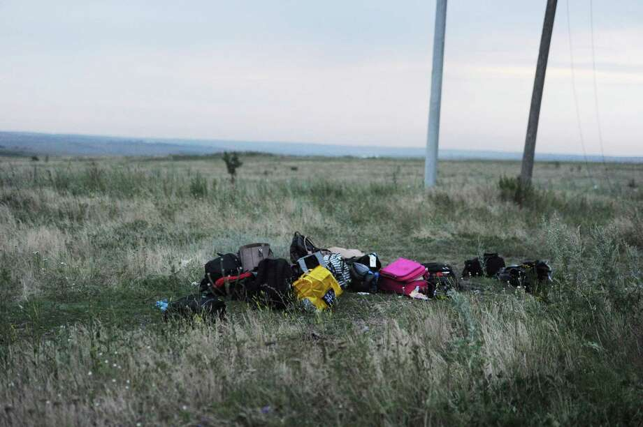 Luggage are pictured on July 17, 2014 on the site of the crash of the Malaysian airliner carrying 295 people from Amsterdam to Kuala Lumpur, near the town of Shaktarsk, in rebel-held east Ukraine. Pro-Russian rebels fighting central Kiev authorities claimed on Thursday that the Malaysian airline that crashed in Ukraine had been shot down by a Ukrainian jet. The head of Ukraine's air traffic control agency said Thursday that the crew of the Malaysia Airlines jet that crashed in the separatist east had reported no problems during flight. Photo: DOMINIQUE FAGET, Wire Photos / AFP