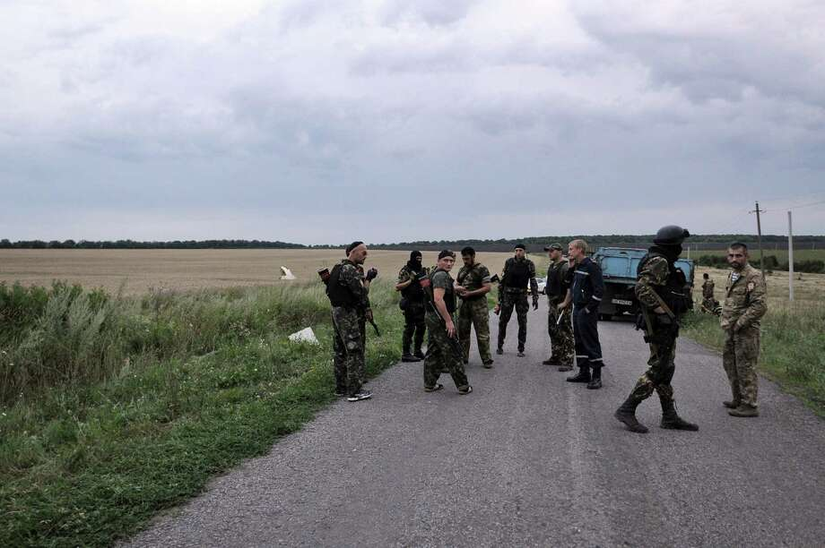 People wearing military fatigues, stand on a road,  on July 17, 2014 at the site of the crash of a malaysian airliner carrying 295 people from Amsterdam to Kuala Lumpur, near the town of Shaktarsk, in rebel-held east Ukraine. Pro-Russian rebels fighting central Kiev authorities claimed on Thursday that the Malaysian airline that crashed in Ukraine had been shot down by a Ukrainian jet. The head of Ukraine's air traffic control agency said Thursday that the crew of the Malaysia Airlines jet that crashed in the separatist east had reported no problems during flight. Photo: DOMINIQUE FAGET, AFP / AFP