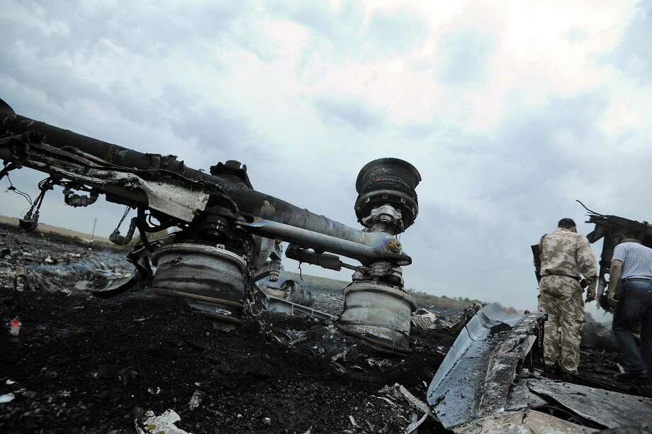 A man wearing military fatigues stands next to the wreckages of the malaysian airliner carrying 295 people from Amsterdam to Kuala Lumpur after it crashed, near the town of Shaktarsk, in rebel-held east Ukraine, on July 17, 2014. Pro-Russian rebels fighting central Kiev authorities claimed on Thursday that the Malaysian airline that crashed in Ukraine had been shot down by a Ukrainian jet. Photo: DOMINIQUE FAGET, AFP / AFP