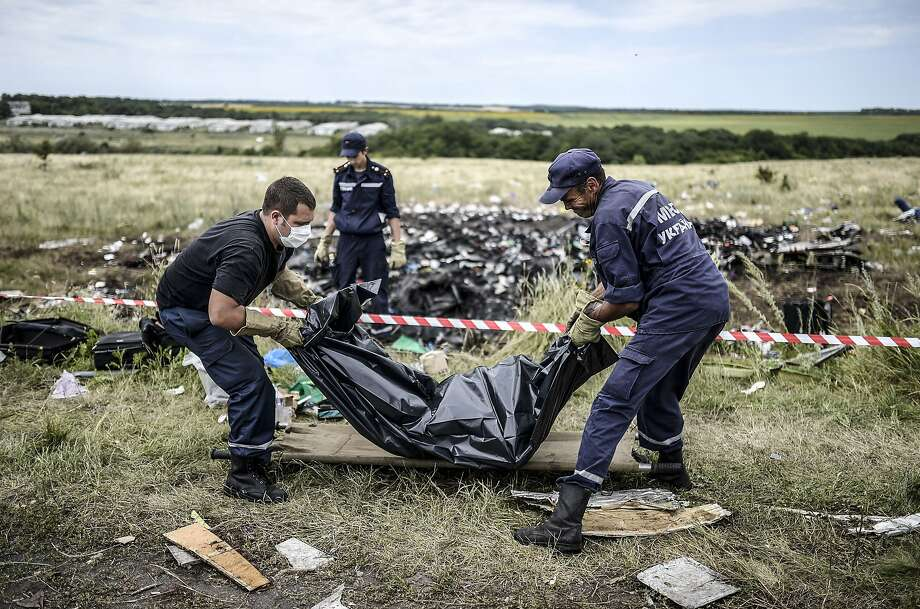 Bodies of victims are collected at the site of the crash of Malaysia Airlines Flight 17 in rebel-held east Ukraine. All 298 people aboard perished. Photo: Bulent Kilic, AFP/Getty Images