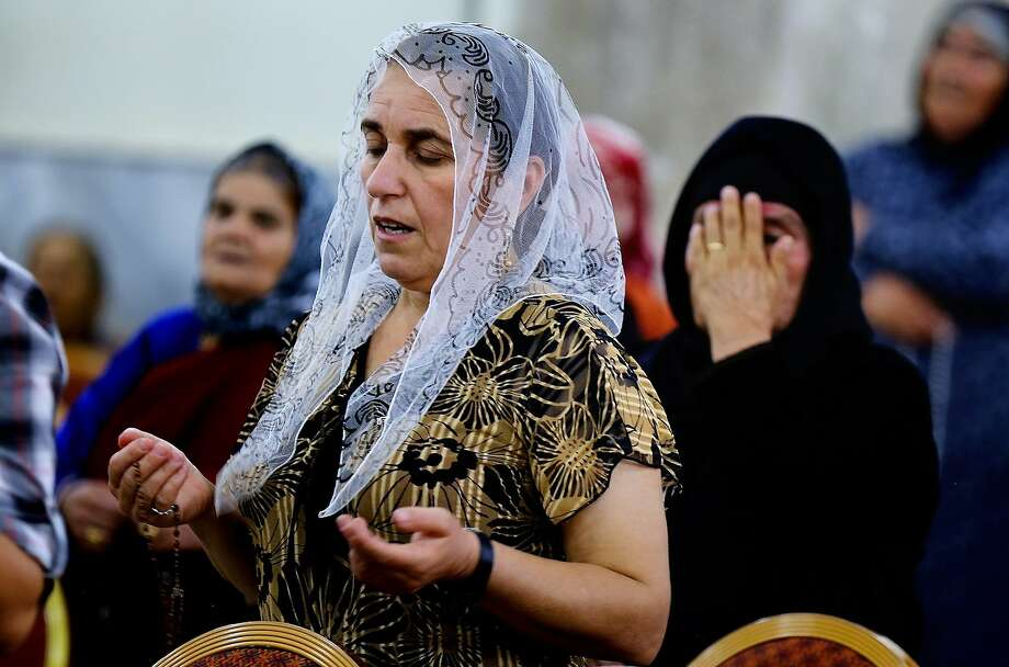 Displaced Christians who fled from violence pray at Mar Aframa church on the outskirts of Mosul. Photo: Uncredited, Associated Press