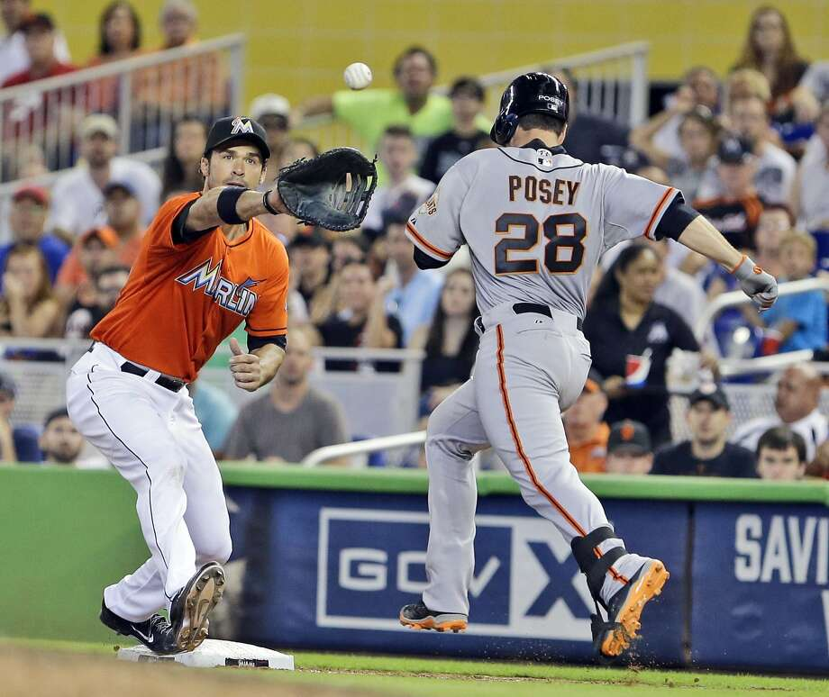 Buster Posey tries to beat the throw to first baseman Garrett Jones. Replay upheld the out call to end the top of the eighth. Photo: Wilfredo Lee, Associated Press