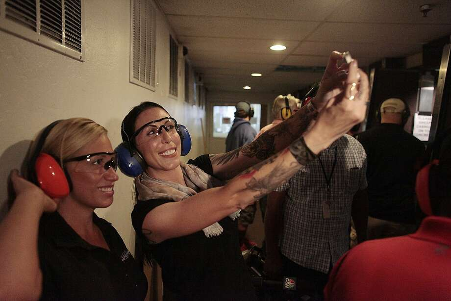 Alexis DeJoria takes a photo with her public relationships manger Allison McCormick at Bullseye on Wednesday, July 16, 2014 in San Rafael, Calif. DeJoria is a Funny Car driver who is a gun enthusiast who is ranked fifth in the Funny Car standings. Photo: James Tensuan, The Chronicle