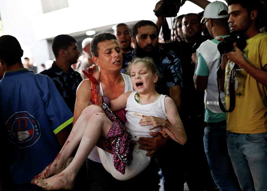 A Palestinian man carries a wounded girl to an emergency room in Gaza City on Sunday. Both sides reported Sunday the highest death tolls so far in the escalating Gaza Strip conflict. Photo: Lefteris Pitarakis, STF / AP