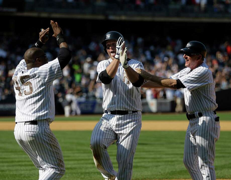 New York Yankees' Brian McCann, center, celebrates with first base coach Mick Kelleher, right, and Zelous Wheeler after his fly ball was dropped, allowing the winning run to score, during the ninth inning of the game at Yankee Stadium Sunday, July 20, 2014 in New York. The Yankees defeated the Reds 3-2. (AP Photo/Seth Wenig) ORG XMIT: NYY113 Photo: Seth Wenig / AP