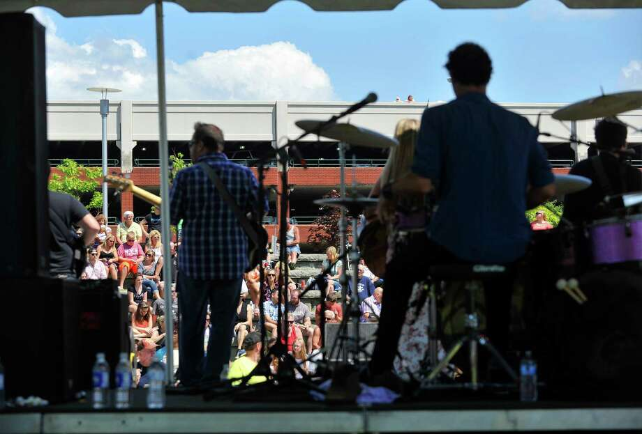 People sit in the park and also on the top level of the parking garage to listen to Chelsea Cavanaugh and her band perform at Riverfront Park during the  annual Troy Pig Out on Sunday, July 20, 2014, in Troy, N.Y.      The event brings in local BBQ teams and also teams from across the United States and Canada for the two-day event.  (Paul Buckowski / Times Union) Photo: Paul Buckowski / 00027844A