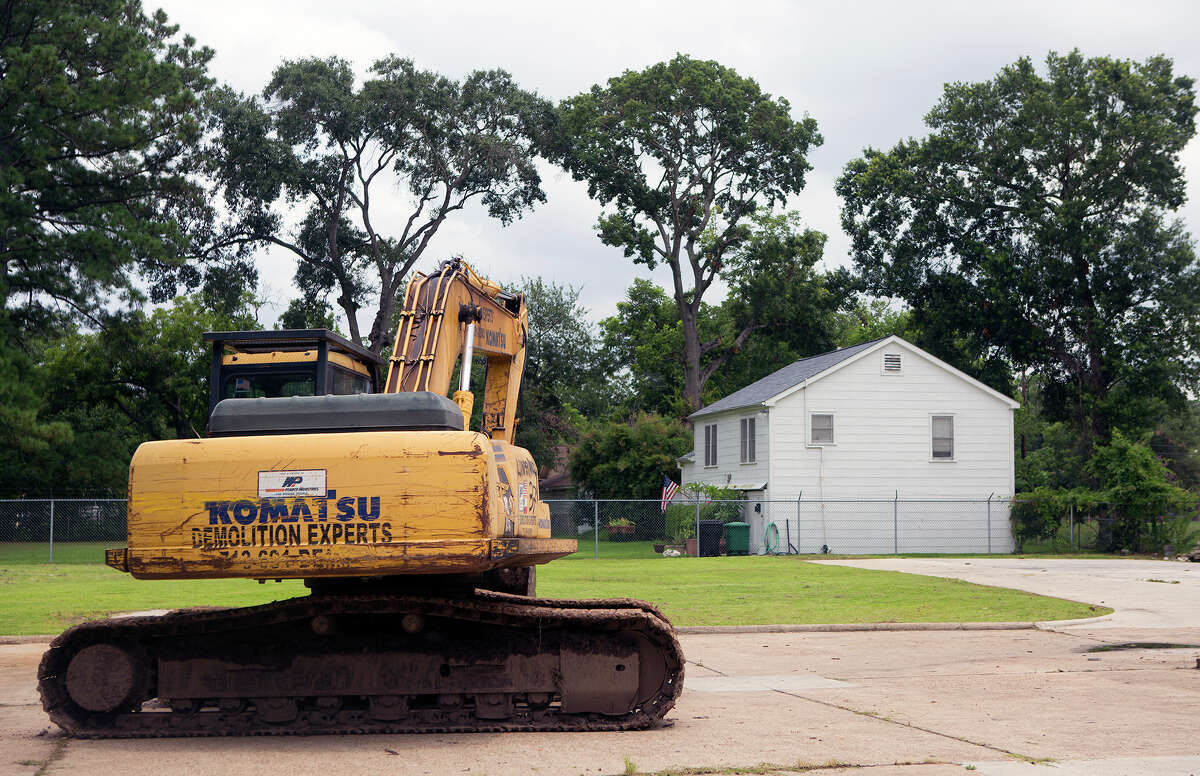 An excavator waits at the site of a future townhome. Changes to city rules allow for an increase in housing density from 16 to 27 units per acre, which officials hope results in more middle-class housing developments.