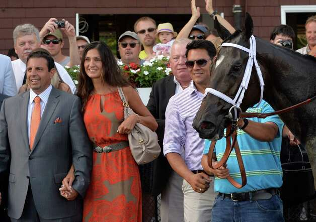 Michael Repole, left stands in the winner's circle with Maria Repole, second from left,  for whom Stopchargingmaria was named after winning the 98th running of the Coaching Club American Oaks Sunday evening July 20, 2014 at the Saratoga Race Course in Saratoga Springs, N.Y.       (Skip Dickstein / Times Union) Photo: SKIP DICKSTEIN