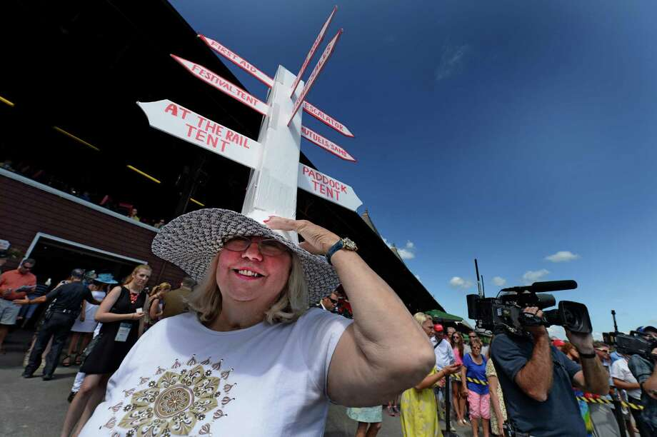 Hat contest entrant Barbara Leyden holds her very tall hat from falling off before the judges get a chance to see her creation Sunday afternoon July 20, 2014 at the Saratoga Race Course in Saratoga Springs, N.Y.       (Skip Dickstein / Times Union) Photo: SKIP DICKSTEIN