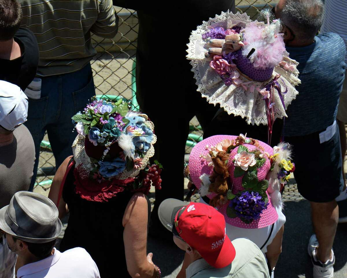 Entrants for the annual hat contest watch a race while waiting for judging Sunday afternoon July 20, 2014 at the Saratoga Race Course in Saratoga Springs, N.Y. (Skip Dickstein / Times Union)
