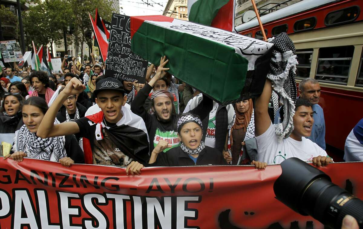 The protesters passed busses in the east bound direction on Market Street Sunday July 20, 2014. Hundreds of people marched in San Francisco, Calif. protesting the military actions by Israel in Gaza in recent days.