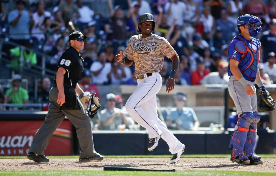 San Diego Padres' Cameron Maybin scores the winning run between New York Mets catcher Travis d'Arnaud and umpire Chris Guccione in the ninth inning of a 2-1 victory in a baseball game Sunday, July 20, 2014, in San Diego.  (AP Photo/Lenny Ignelzi) ORG XMIT: CALI112 Photo: Lenny Ignelzi / AP