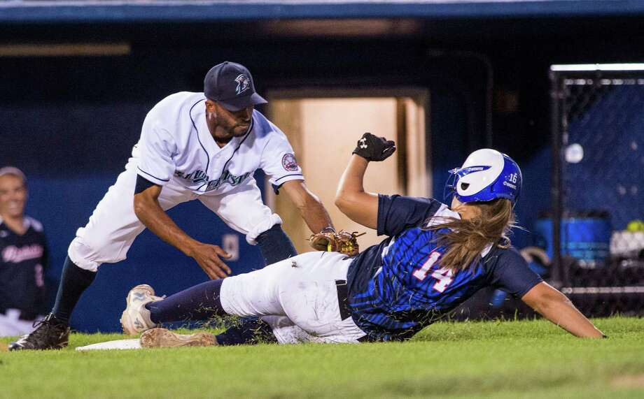 Cassie Ruscz of the Stratford Brakettes slides safely into third base as Bridgeport Bluefish third baseman Joe Bateman doesn't get the tag on her in time during a softball game played at the Ballpark at Harbor Yard, Bridgeport, CT on Sunday, July, 20th, 2014. Photo: Mark Conrad / Connecticut Post Freelance