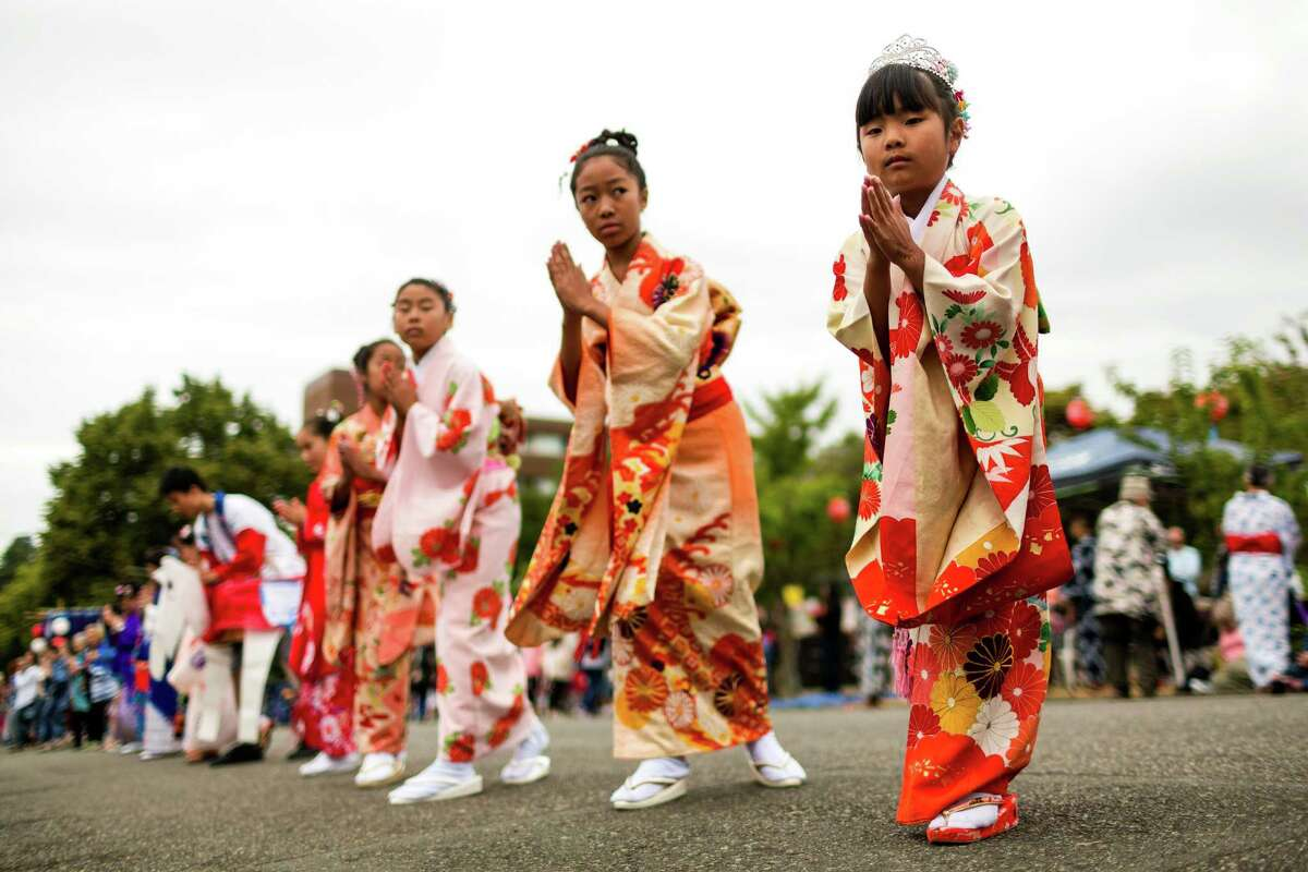 Dressed in traditional garb, young women dance their way up a closed-off city block during the 82nd annual traditional Buddhist celebration of Bon Odori Sunday, July 20, 2014, in Seattle, Wash. The two-day festival welcomes the spirit of ancestors back from the spirit world to this world.