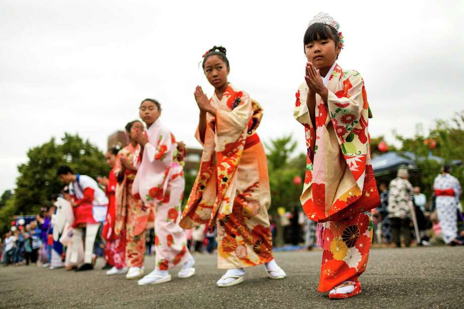 Dressed in traditional garb, young women dance their way up a closed-off city block during the 82nd annual traditional Buddhist celebration of Bon Odori Sunday, July 20, 2014, in Seattle, Wash. The two-day festival welcomes the spirit of ancestors back from the spirit world to this world. Photo: JORDAN STEAD, SEATTLEPI.COM / SEATTLEPI.COM