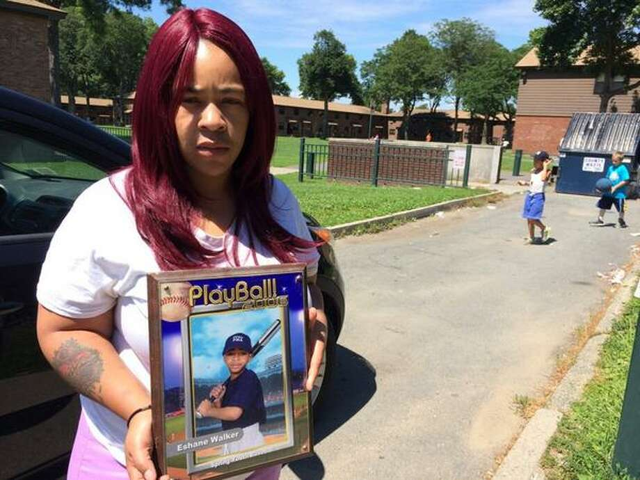 Tyronda Walker poses outside her Griswold Heights apartment in Troy July 20, 2014 with a picture of her now 16-year-old son, E'Shane, who was stabbed to death at a party in Lansingburgh two days before. (Photo by Lauren Stanforth)