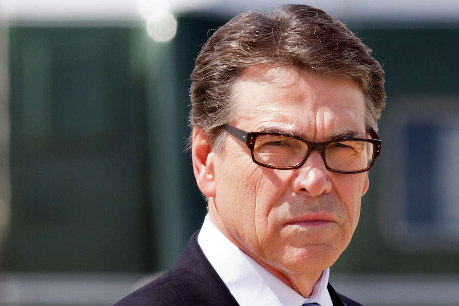 Texas Gov. Rick Perry waits to meet President Barack Obama on arrival in Dallas where they will attend a meeting on immigration, Wednesday, July 9, 2014. (AP Photo/Jacquelyn Martin) Photo: Jacquelyn Martin, STF / AP