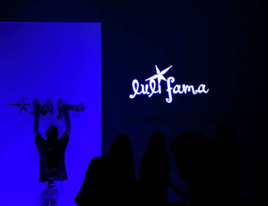 A worker prepares for the Luli Fama collection during the Mercedes-Benz Fashion Week Swim show, Sunday, July 20, 2014, in Miami Beach, Fla. Photo: J Pat Carter, AP / AP