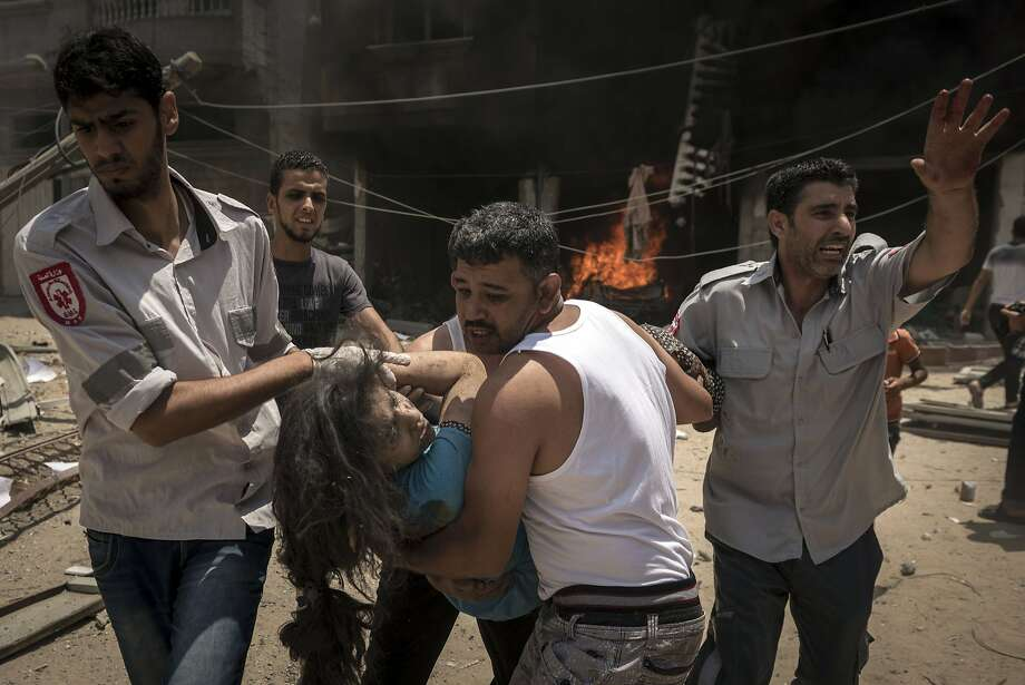Palestinian emergency workers carry a woman from a house that was hit by an Israeli airstrike in Rafah, in the Gaza Strip, on Sunday, July 20, 2014. Casualties grew on both sides as the Israeli military pressed on with its campaign aimed at quelling rocket fire into Israel and exposing and destroying tunnels. (Sergey Ponomarev/The New York Times) Photo: Sergey Ponomarev, New York Times